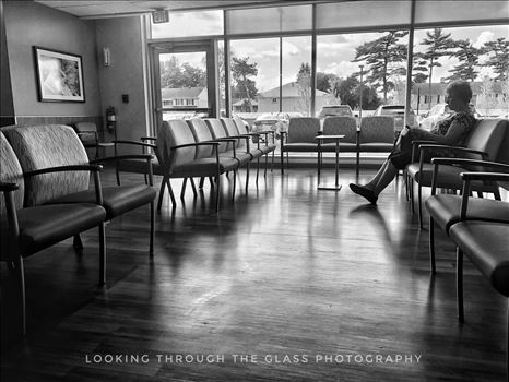 Silhouette of a woman down in black and white in a hospital waiting room.